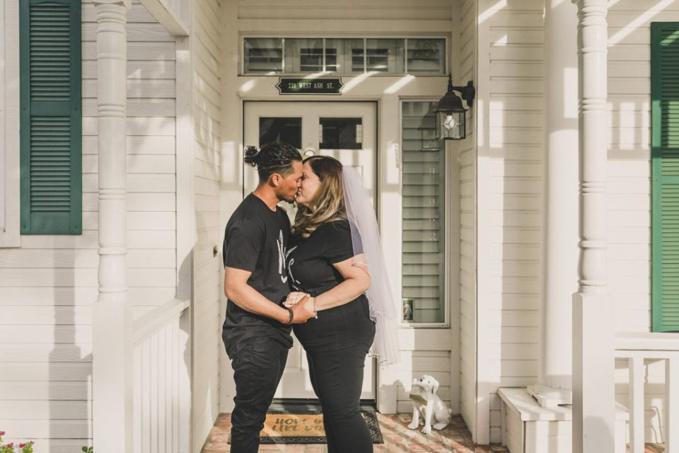Taylor Made Photography photographs couple on the front steps of their home kissing