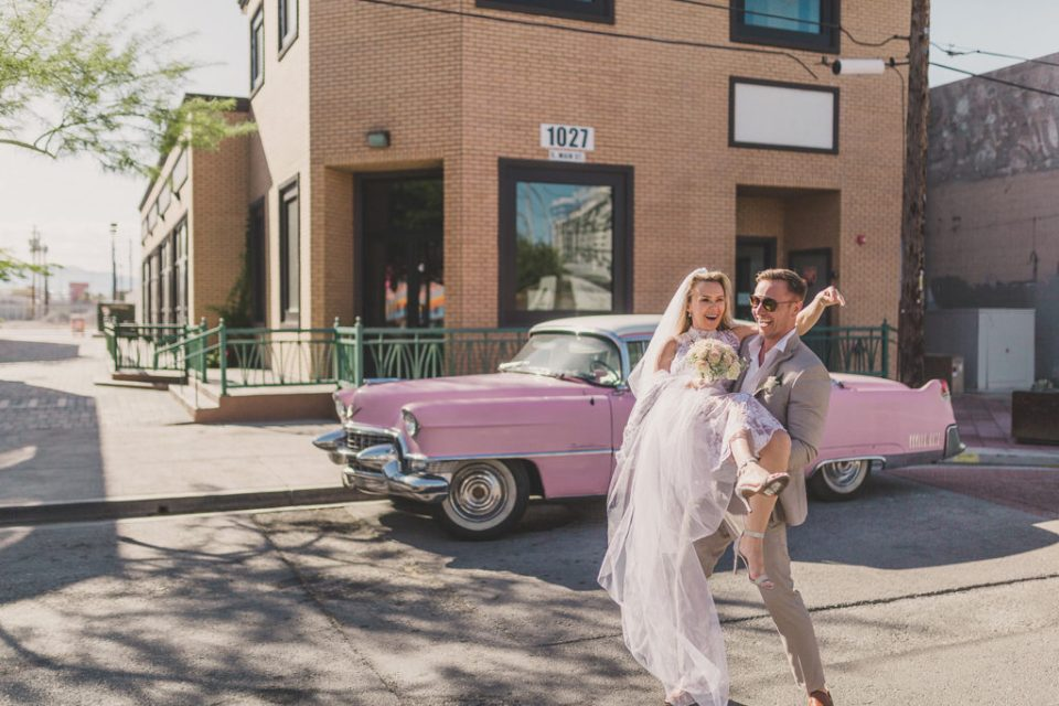 bride and groom pose near pink Cadillac photographed by Taylor Made Photography