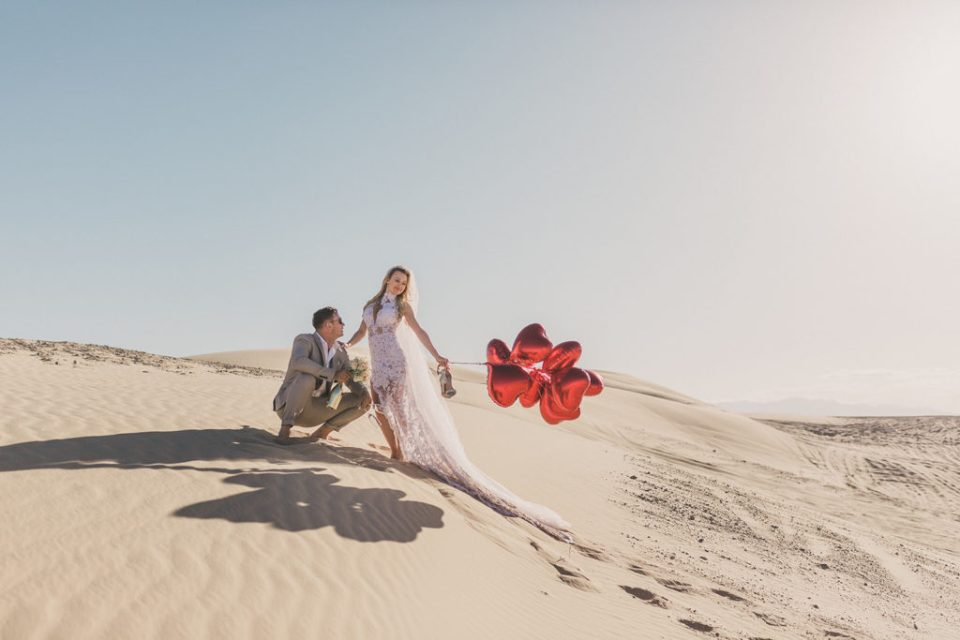 Taylor Made Photography captures bride and groom holding red balloons on sand dunes