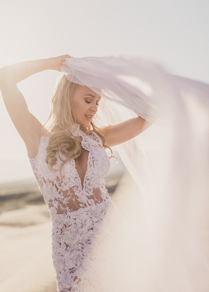 Taylor Made Photography captures bride playing with veil on sand dunes