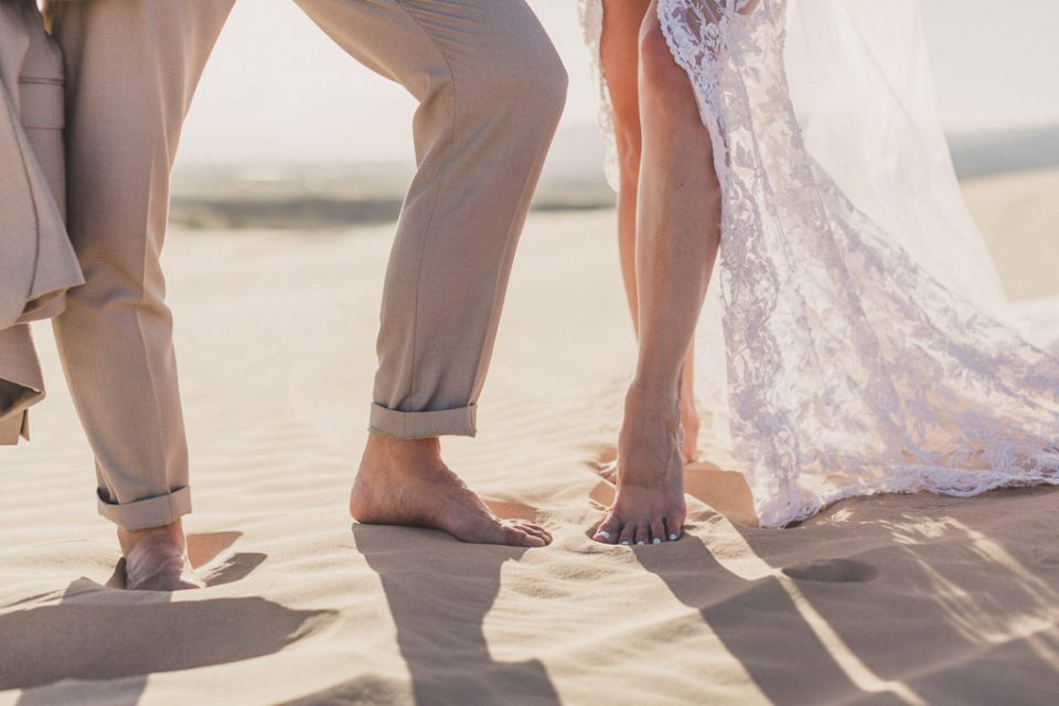 bride and groom stand in the sand of Las Vegas photographed by Taylor Made Photography