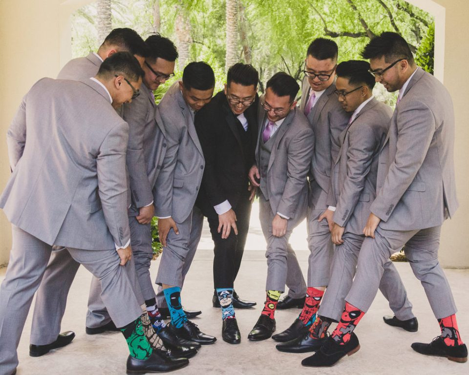 groom and groomsmen show off socks before wedding day with Taylor Made Photography