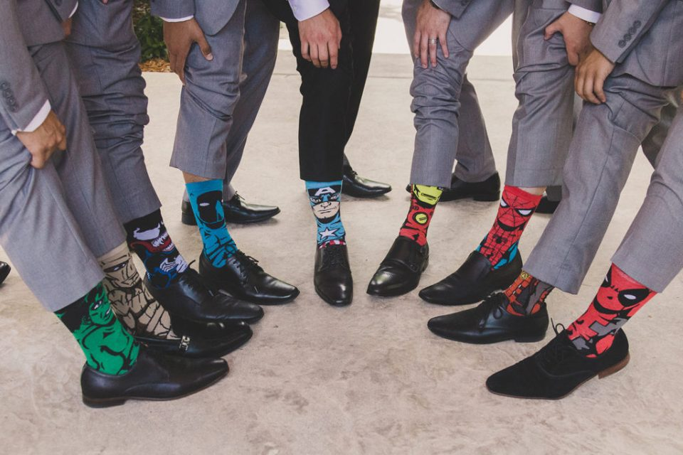 groomsmen show off playful socks during wedding prep with Taylor Made Photography