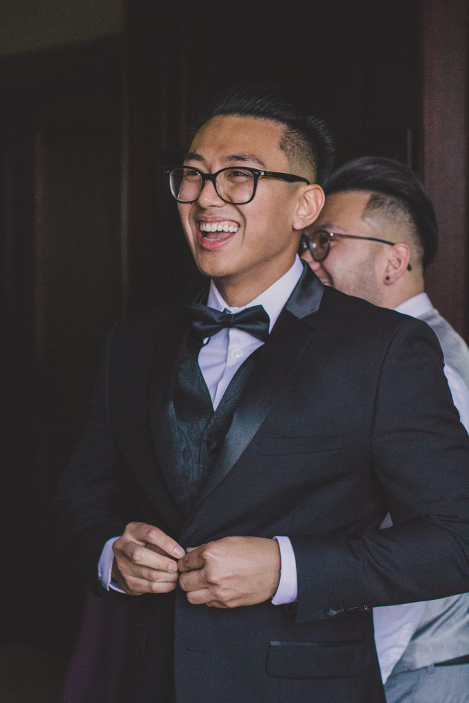 groom laughs during wedding prep photographed by Taylor Made Photography