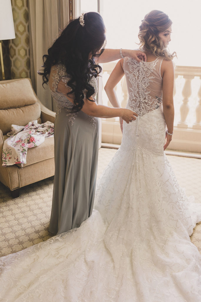 mother of the bride helps with wedding gown photographed by Taylor Made Photography