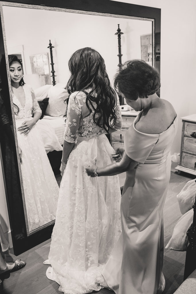bride gets into wedding dress with mother photographed by Taylor Made Photography