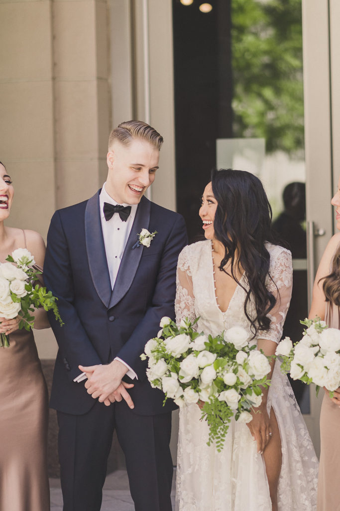 bride and groom smile at each other while posing with the bridal party
