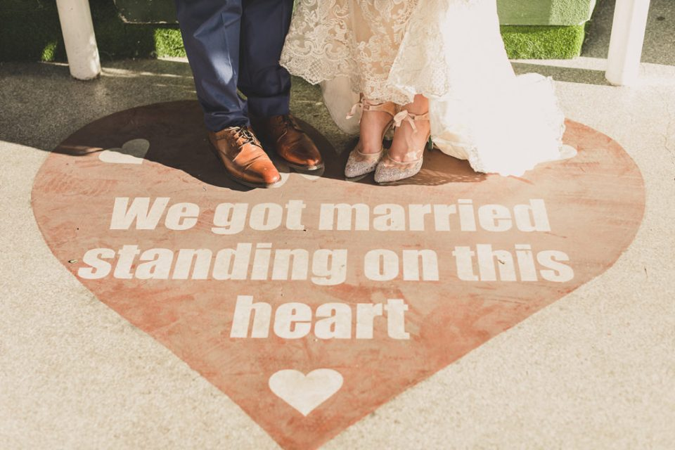 "bride and groom's toes and ""We Got Married Standing on This Heart"" display photographed by Taylor Made Photography"