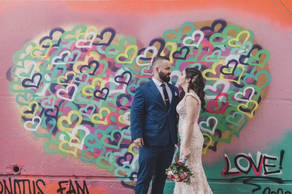 bride and groom pose by neon heart mural photographed by Taylor Made Photography