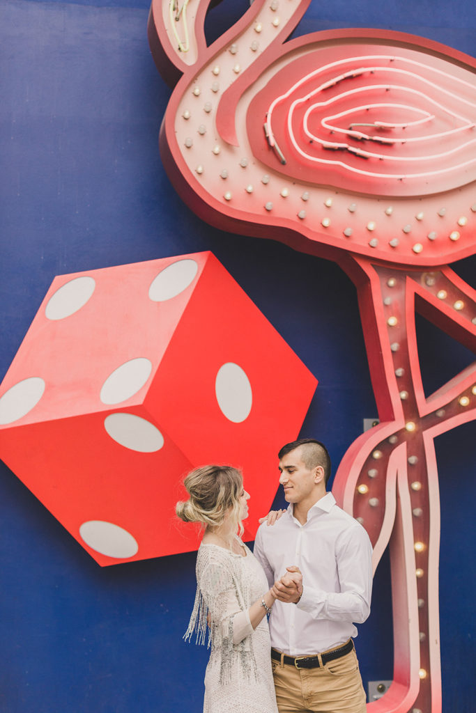 bride and groom dance by mural with dice and flamingo photographed by Taylor Made Photography