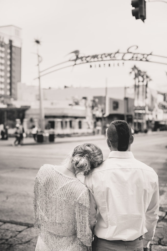 bride and groom look at Fremont Street during engagement portraits with Taylor Made Photography