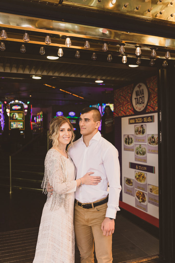 bride and groom pose near casino on Fremont Street with Taylor Made Photography