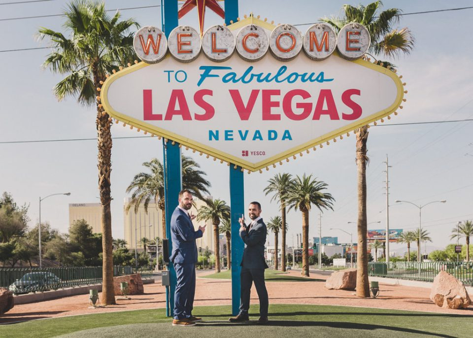 Taylor Made Photography captures grooms goofing off during elopement portraits by neon Las Vegas sign