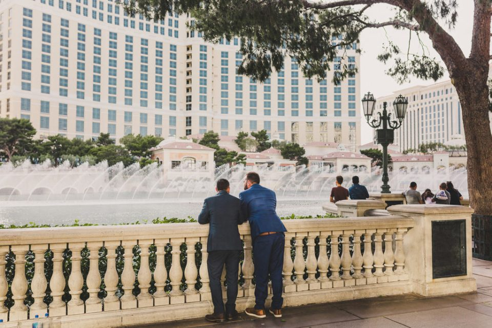couple eloping poses in front of Bellagio Fountains