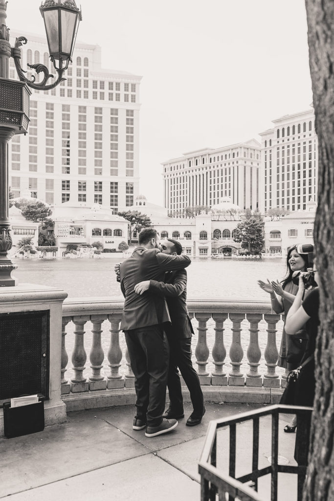 grooms embrace after elopement in front of Bellagio Fountain photographed by Taylor Made Photography