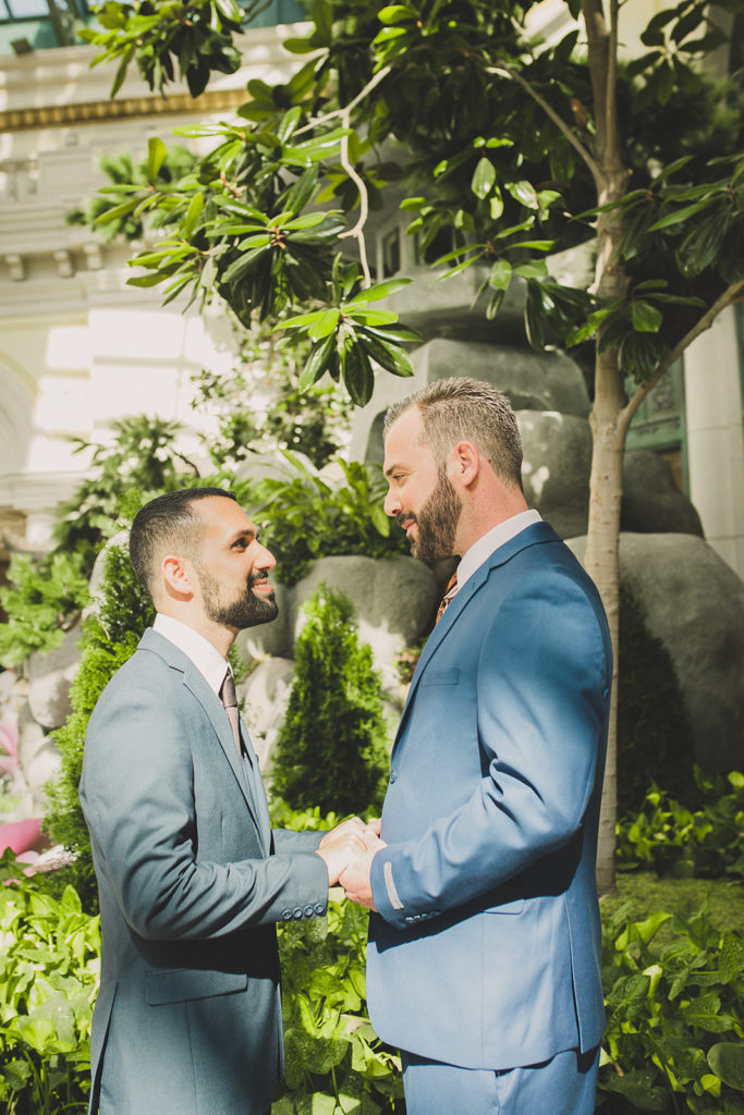 grooms look at each other during elopement portraits with Taylor Made Photography