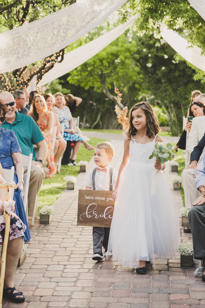 ring bearer and flower girl walk down the aisle at the Grove photographed by Taylor Made Photography