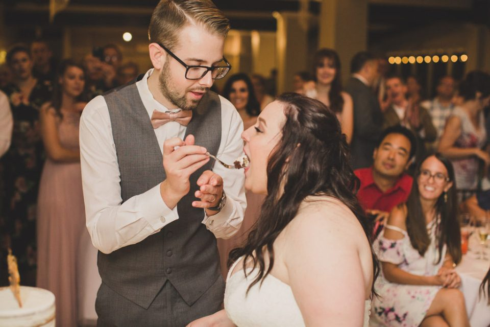 groom feeds bride a piece of cake photographed by  Taylor Made Photography