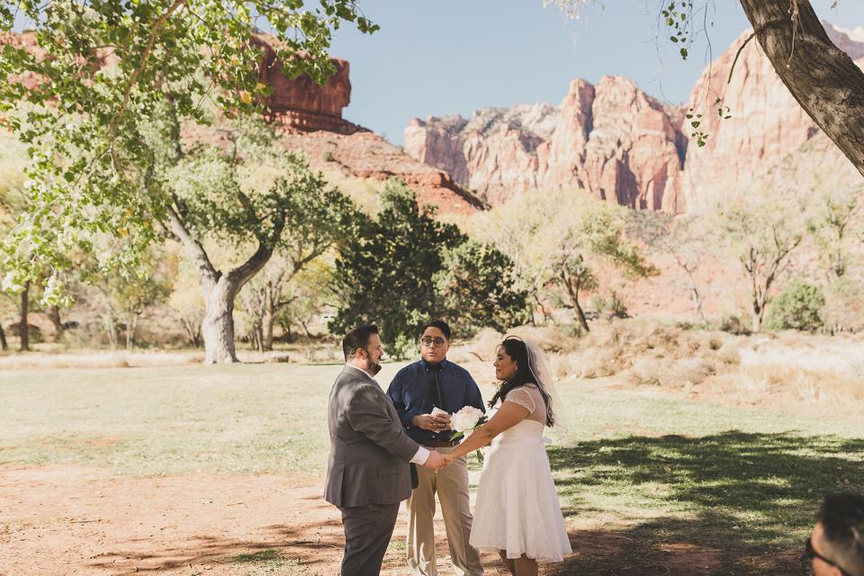 bride and groom exchange vows outside Zion National Park photographed by Taylor Made Photography