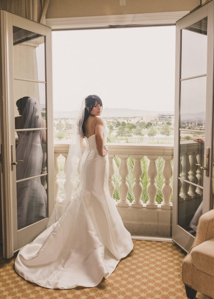 bride looks out balcony at JW Marriott Las Vegas before wedding day