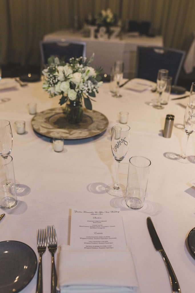wedding reception table with white flower centerpieces