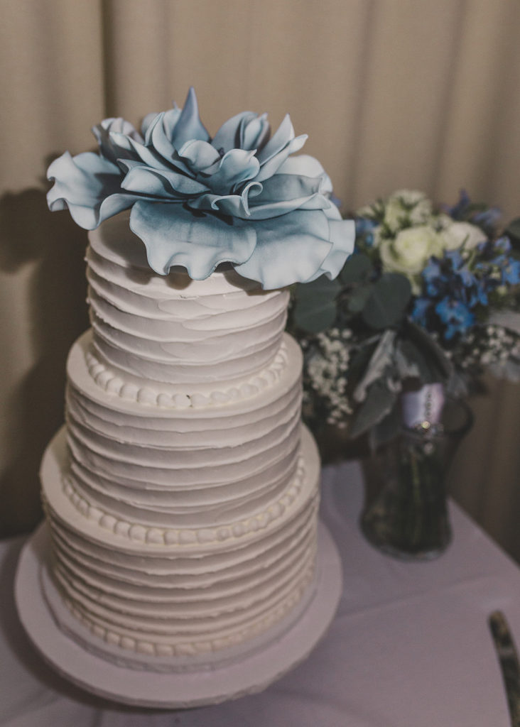 wedding cake with blue flower on top