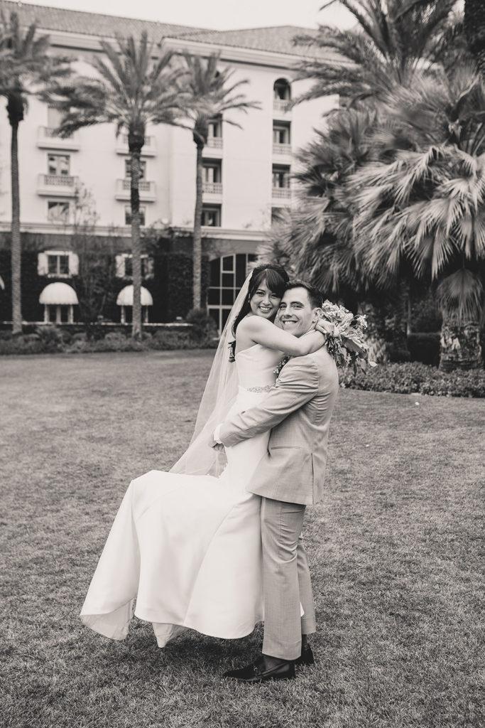groom lifts bride during wedding portraits in Las Vegas