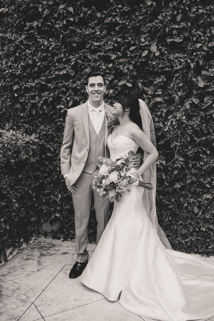 bride and groom pose by hedge at JW Marriott Las Vegas