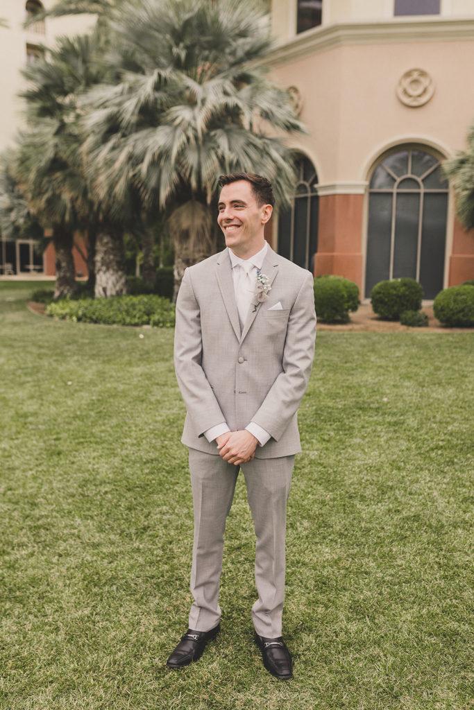groom in grey suit waits for first look in Las Vegas