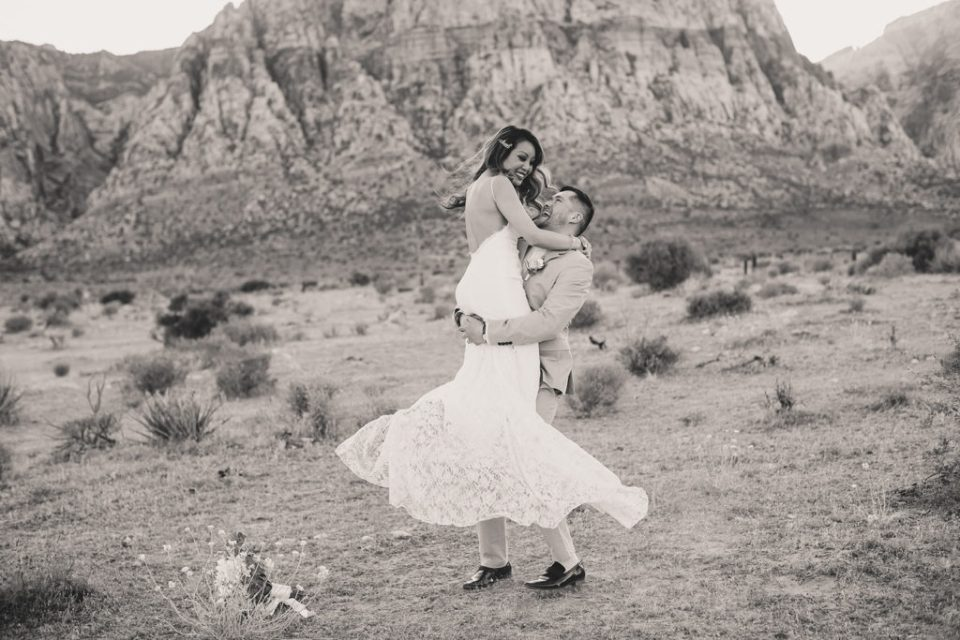 groom lifts bride and twirls around in Red Rock Canyon with Taylor Made Photography