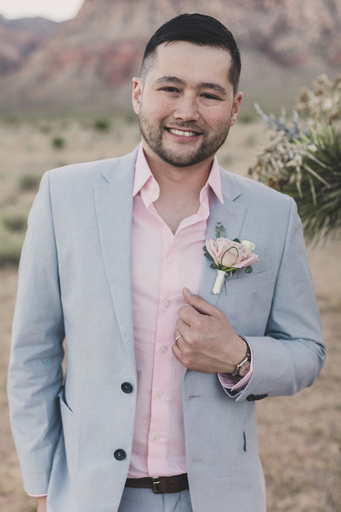 groom in grey jacket and pink shirt poses for Taylor Made Photography