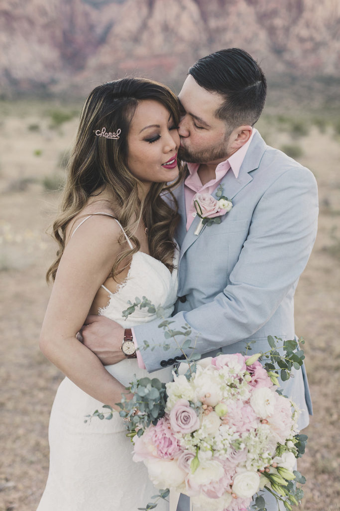 bride and groom embrace during portraits in Red Rock Canyon with Taylor Made Photography
