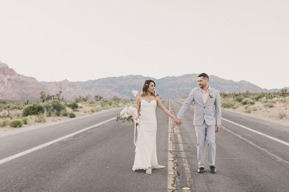 bride and groom walk on road in Las Vegas photographed by Taylor Made Photography
