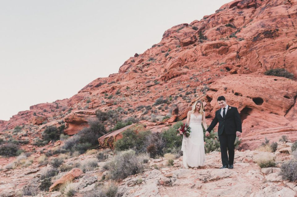 newlyweds walk in front of Red Rock Canyon with Taylor Made Photography