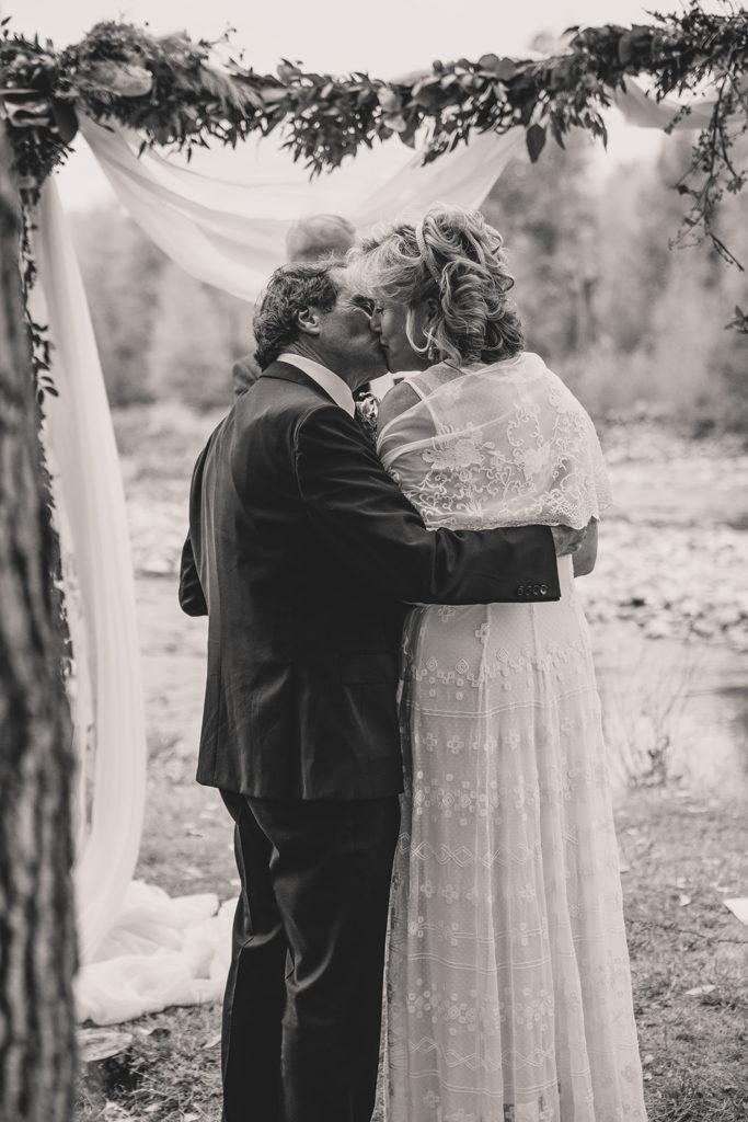 newlyweds kiss under wood arbor at Freestone Lodge