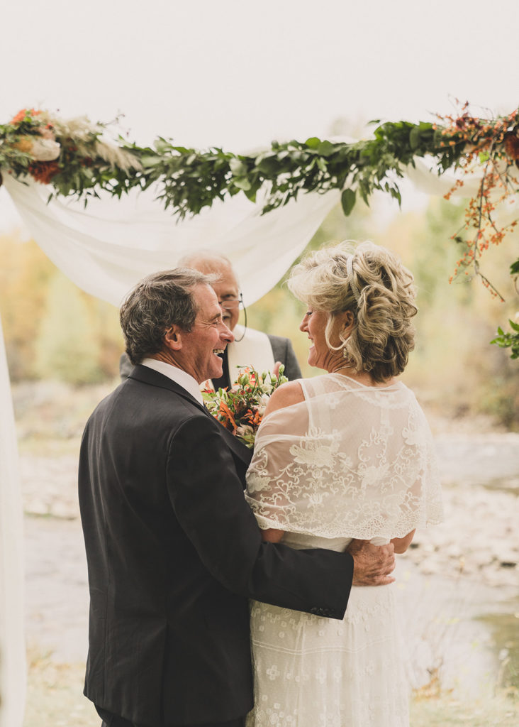 groom hugs bride during fall wedding ceremony along riverfront