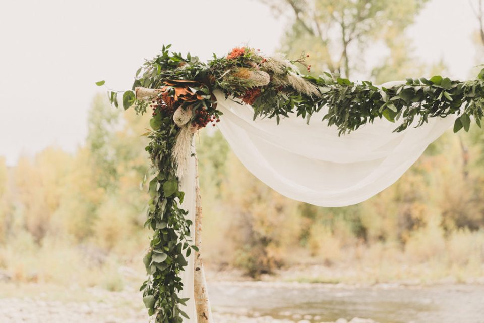 wood arbor with floral details for fall wedding at Freestone Lodge