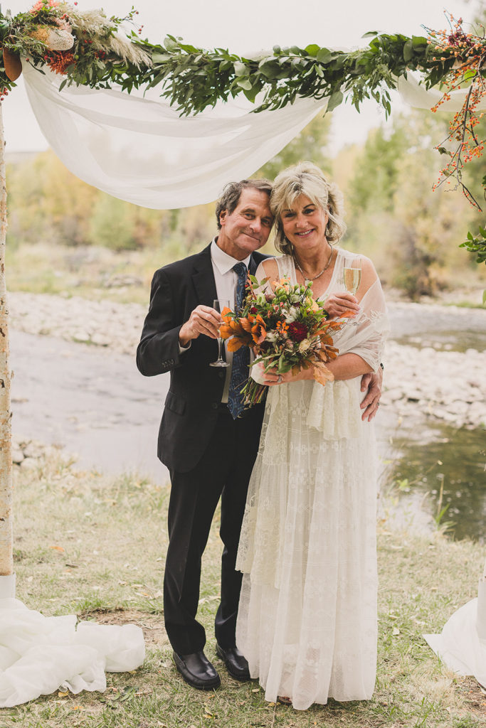 bride and groom toast after riverfront wedding in Utah