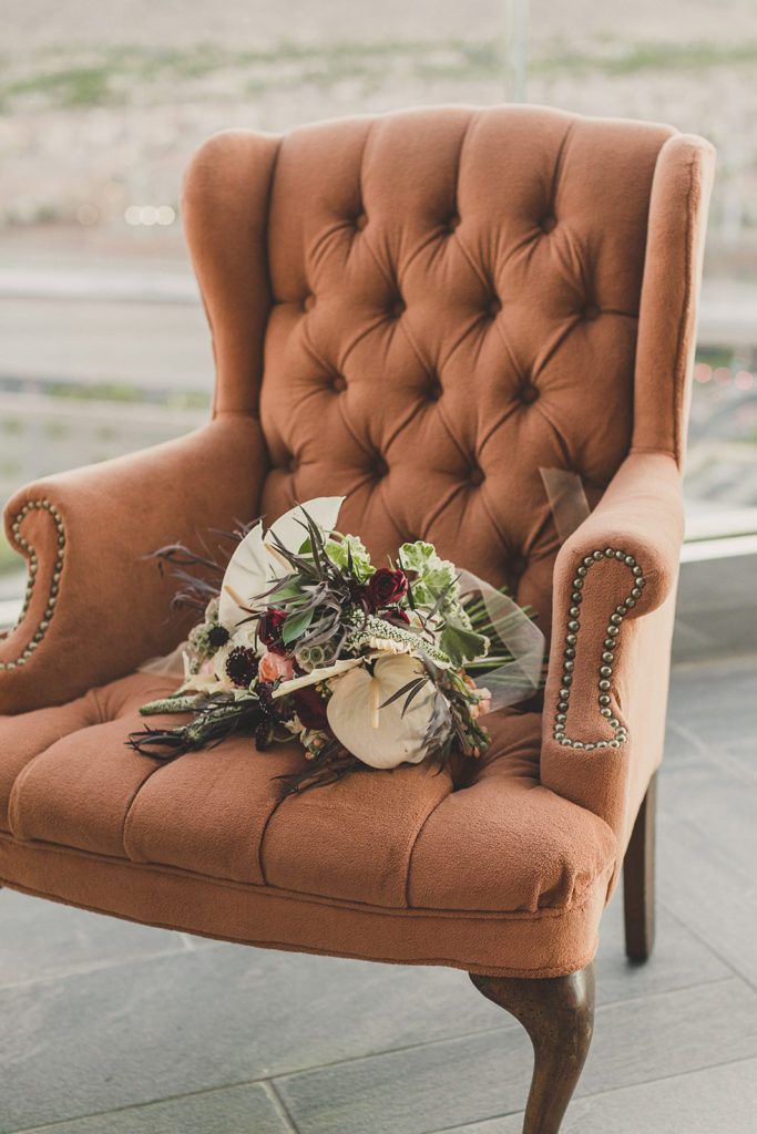 wedding bouquet rests on rust colored armed chair