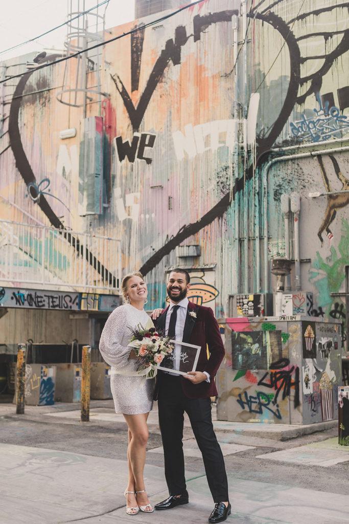 bride and groom hold acrylic wedding sign