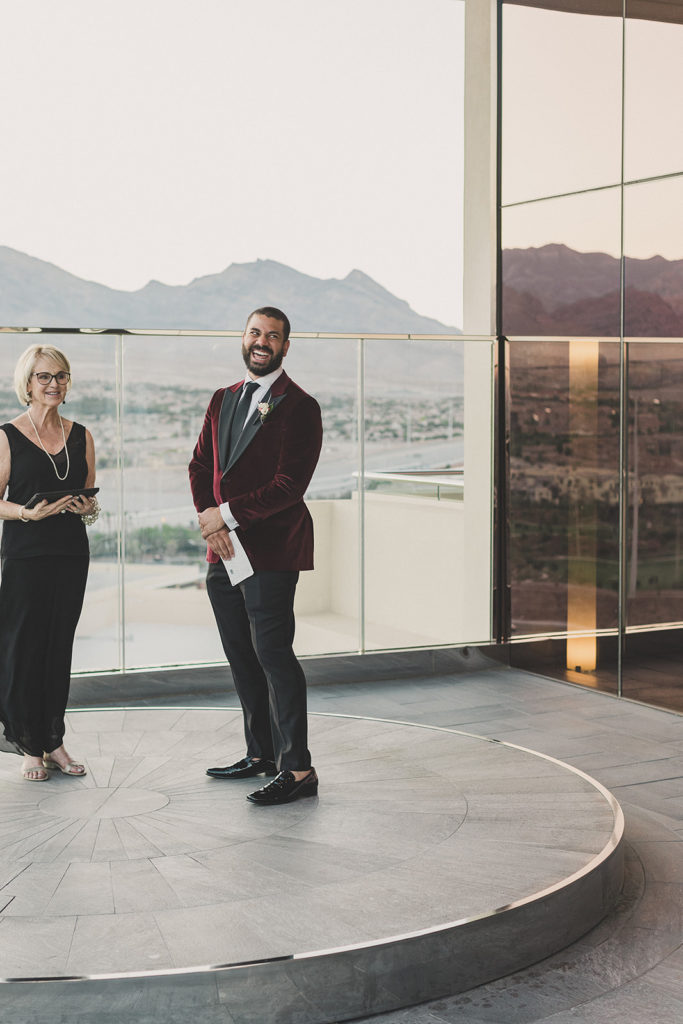 groom watches bride enter Red Rock Resort wedding ceremony