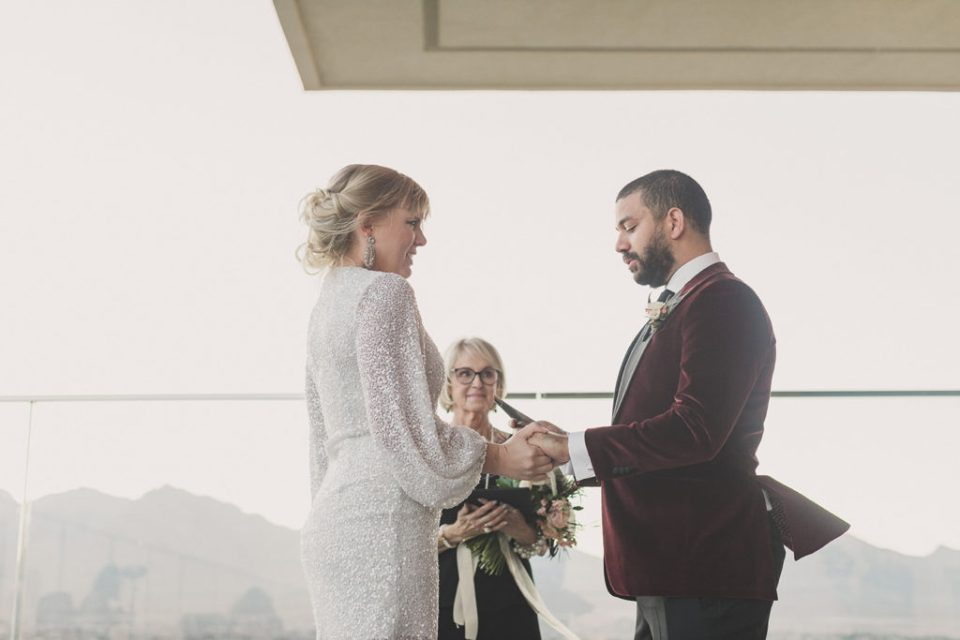 couple exchanges vows during modern wedding ceremony looking over Las Vegas