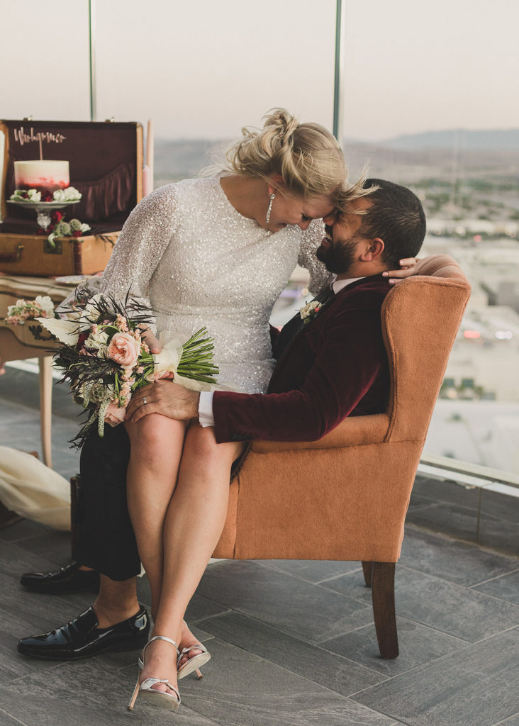 bride sits on groom's lap on roof at Red Rock Resort