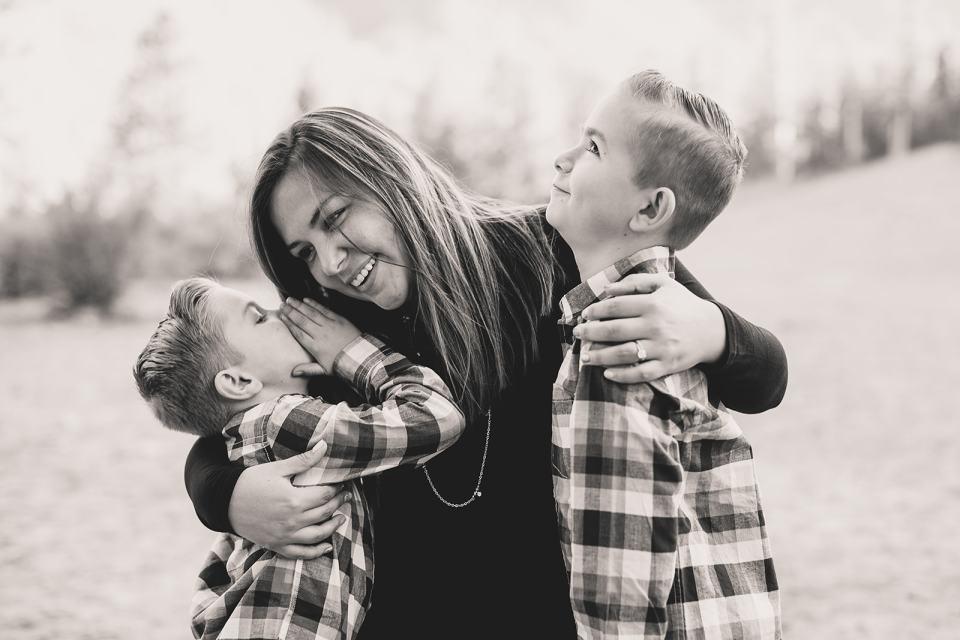 boys tell mom secrets during family photos