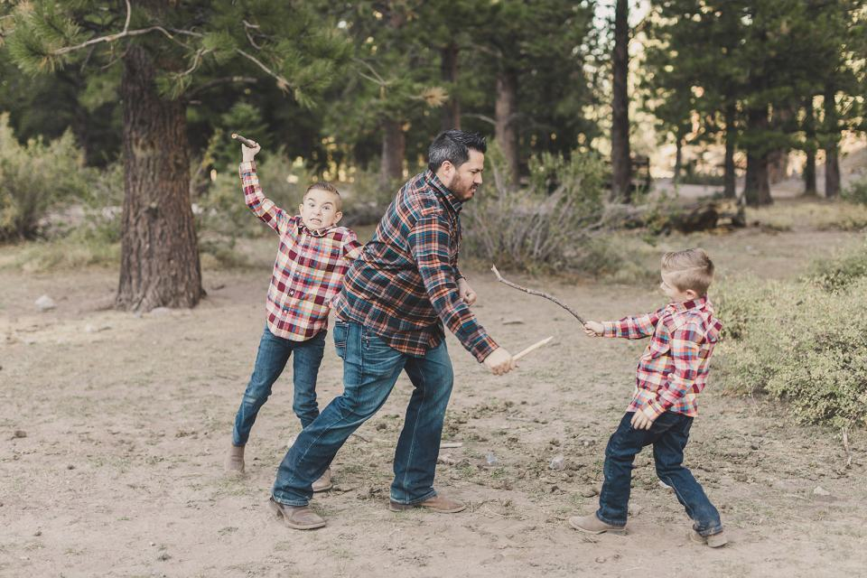 sons play with sticks with dad during Las Vegas Family Portraits