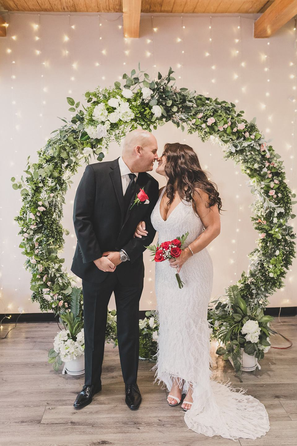 bride and groom pose by greenery circular arbor