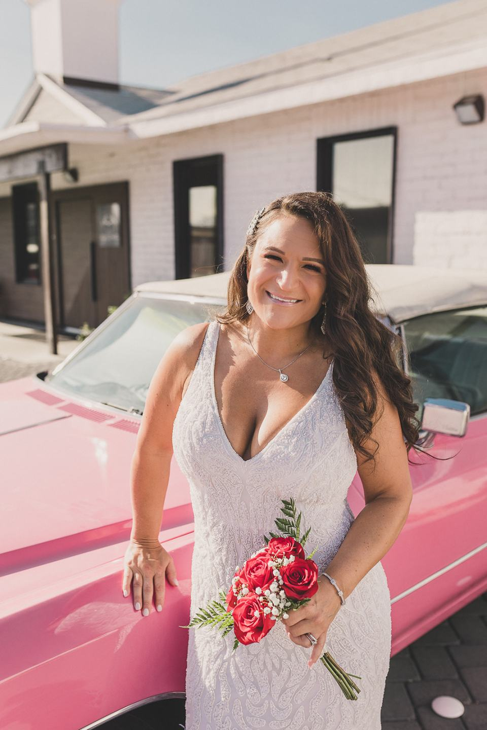 bride poses by pink Cadillac