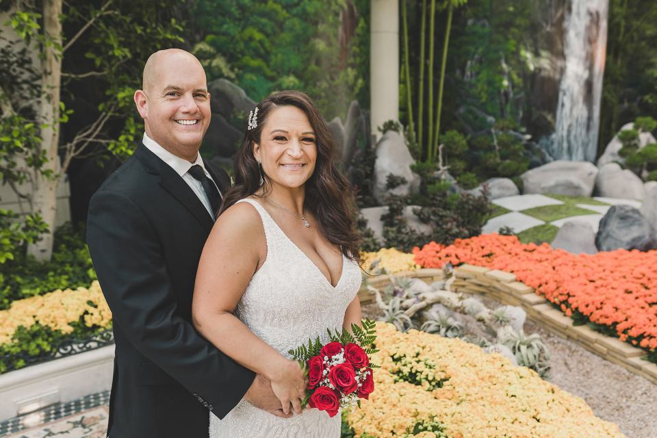 bride and groom pose in gardens at Bellagio Hotel