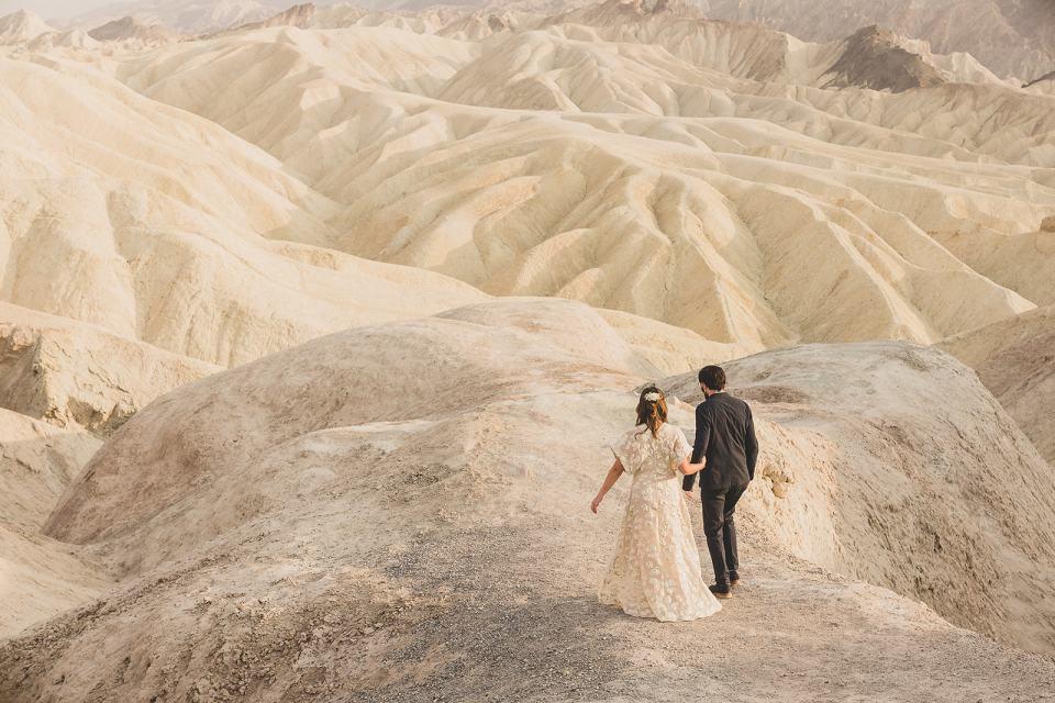 newlyweds walk through hills at Zabriskie Point