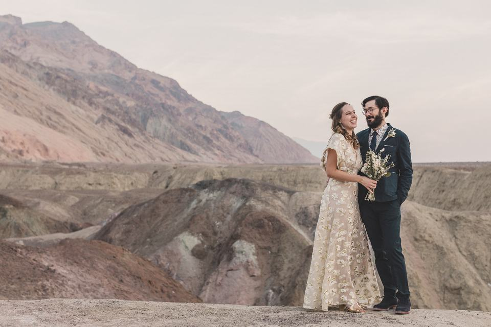 bride and groom pose in front of natural wonders at Death Valley